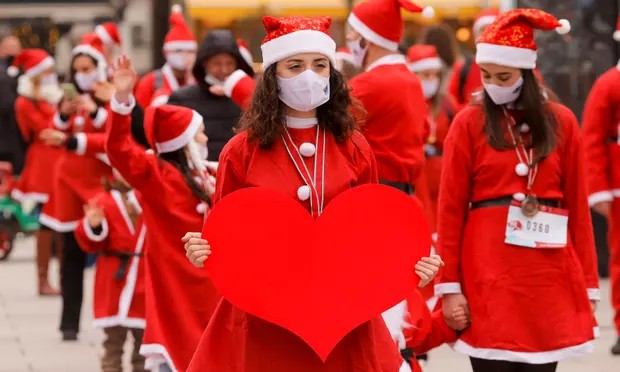 People wear Santa Claus costumes and face masks take part in a charity event in Pristina, Kosovo. Photograph: Valdrin Xhemaj/EPA