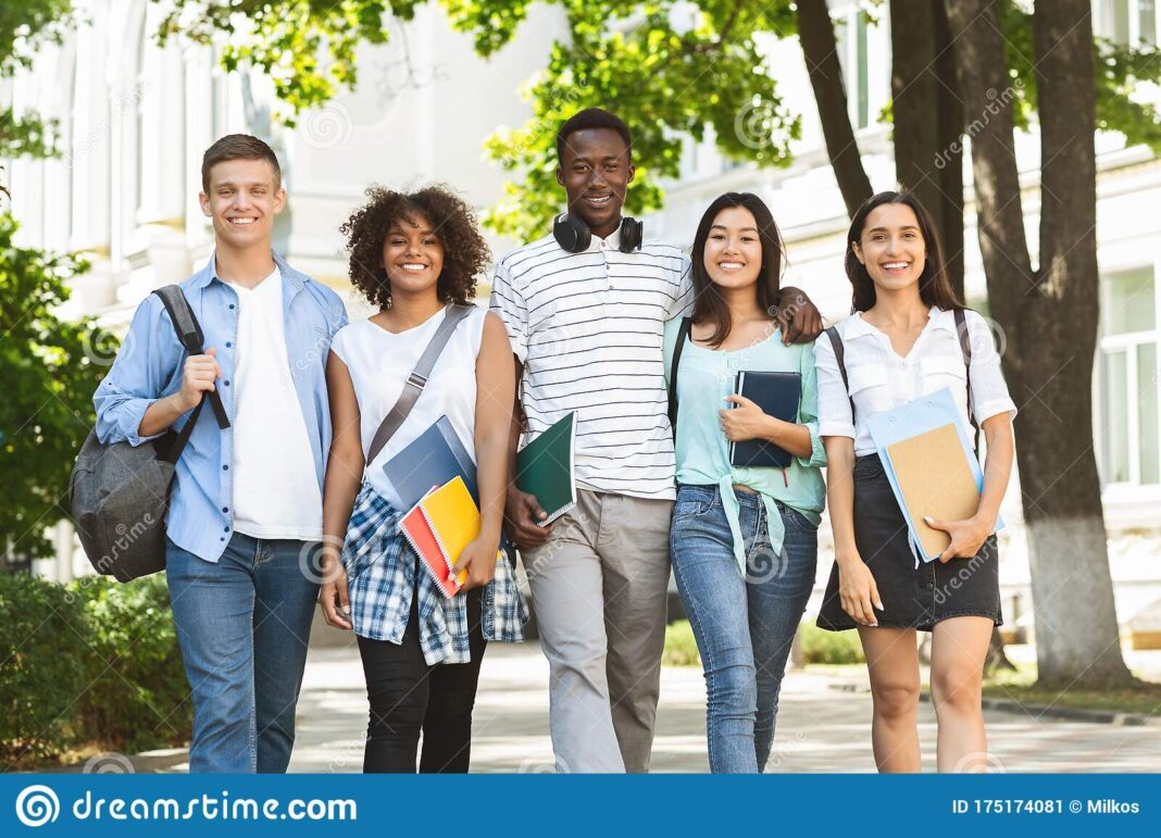 Cheerful College Students Walking Out Campus Together Posing Outdoors Camera Having Break Classes Free Space 175174081